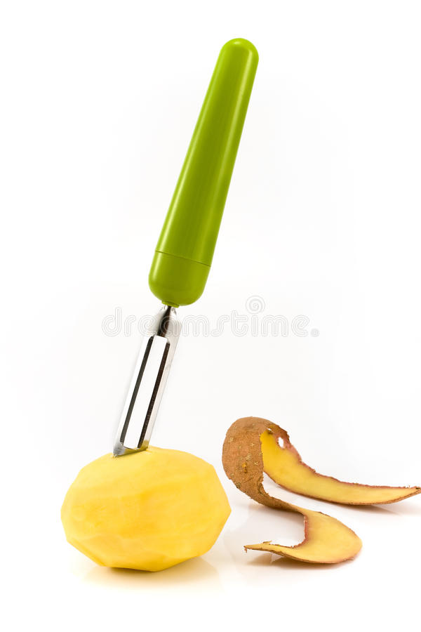 Potatoes with vegetable peeler royalty free stock photo