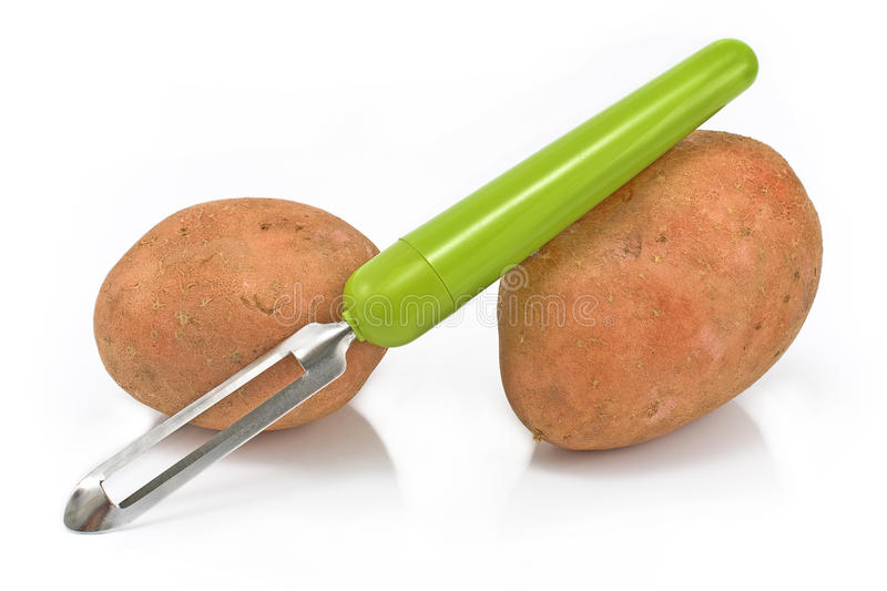 Potatoes with vegetable peeler royalty free stock photos