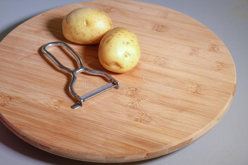 Potatoes on wooden board with a vegetable peeler, close up stock photo
