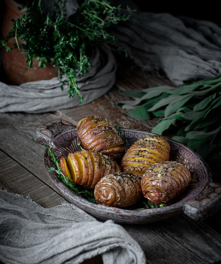 Potatoes in a wooden plate, baked with herbs and spices. Food photography in a rustic style.  royalty free stock photos