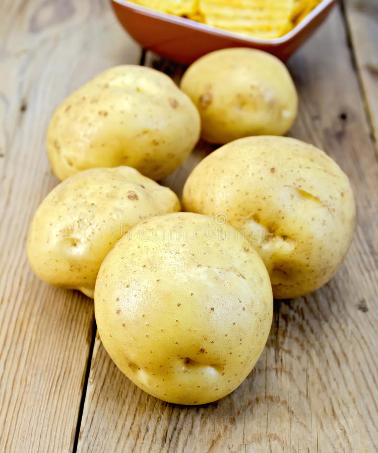 Potatoes yellow and chips on wooden board royalty free stock photography