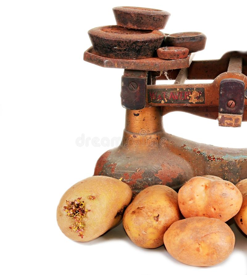 Potatos. Image of an old scales with potatos on a white background royalty free stock photos