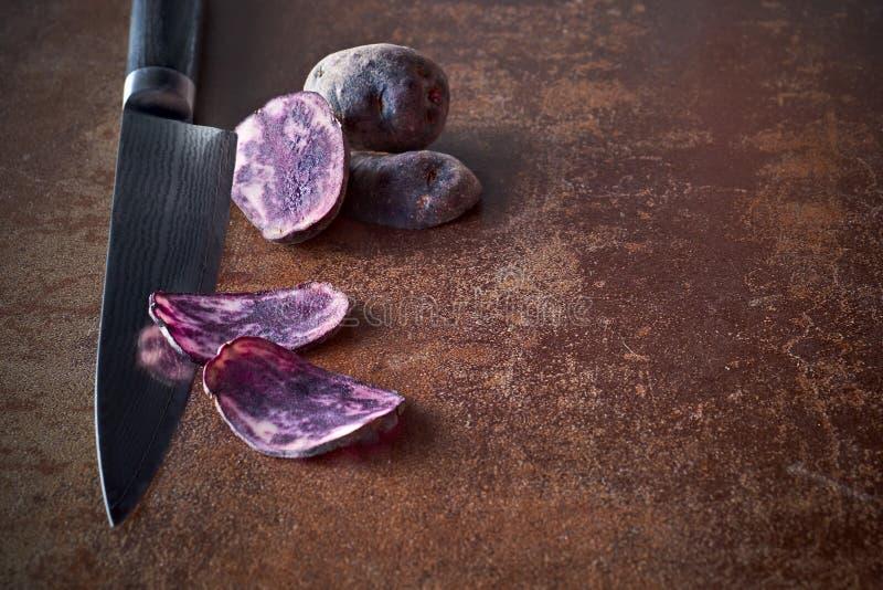 Potatos púrpuras cortados, dos rebanadas en el cuchillo y dos potatos enteros fotos de archivo libres de regalías