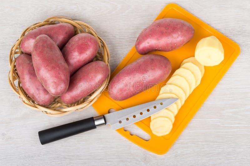 Potatos vermelhos crus na cesta de vime e no potatoe desbastado fotos de stock