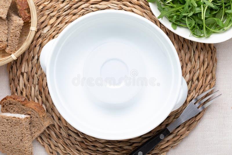 Pote blanco vacío En mantel beige delicado Incluye el pan y el arugula verde imagen de archivo