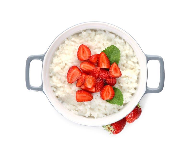 Pote con el pudín y la fresa deliciosos de arroz en el fondo blanco imagen de archivo libre de regalías