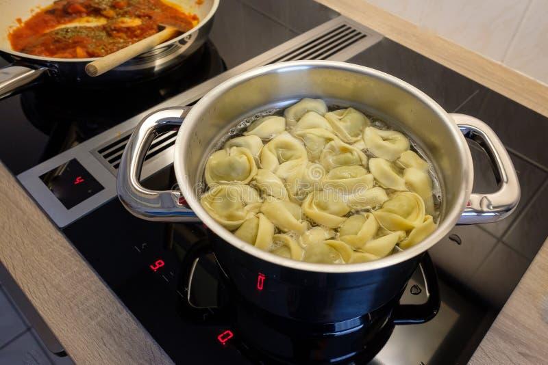 Pote con el tortellini y la cacerola con la salsa de tomate fotos de archivo libres de regalías