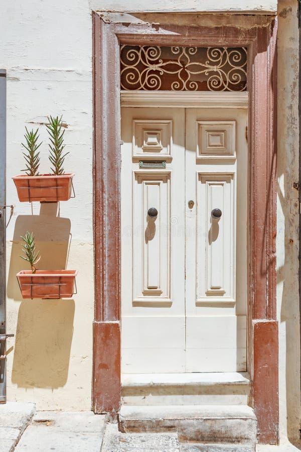 Pote con las plantas de los succulents en la puerta de la entrada a la casa con una ranura para recibir letras y el correo en la  imagenes de archivo