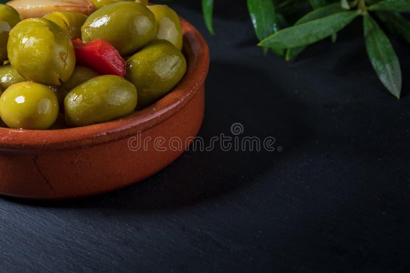 Pote de arcilla con las aceitunas del artesano preservadas en aceite de oliva virginal adicional, vinagre, especias con las pimie fotografía de archivo libre de regalías