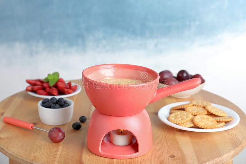 Pote de cerámica con la 'fondue' de chocolate blanca imagen de archivo libre de regalías