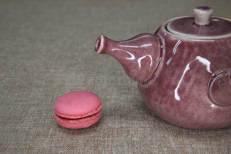 pote de cerámica del té y un pedazo de macarrones imágenes de archivo libres de regalías