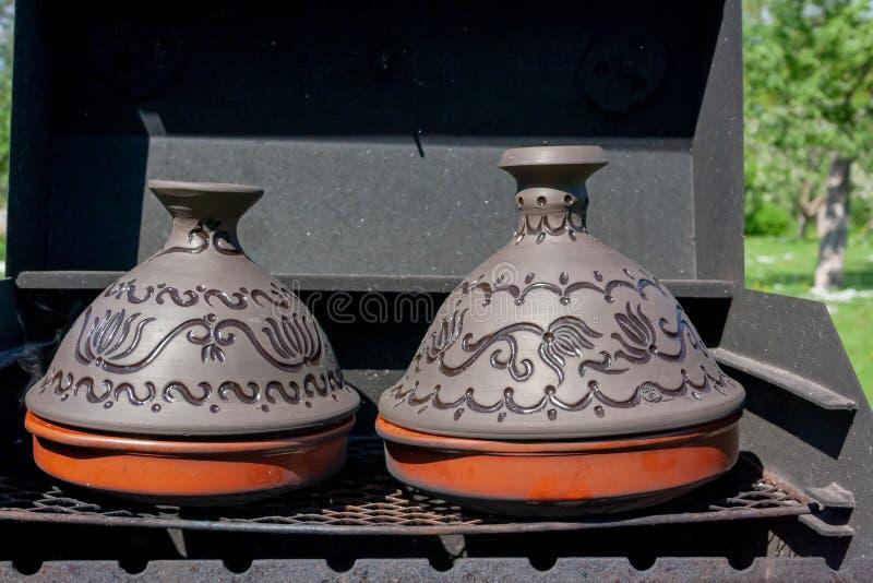 Pote de cer?mica marroqu? tradicional del tajine o del tagine en un d?a de verano soleado de la parrilla negra imagenes de archivo