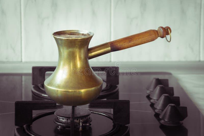 Pote de cobre turco viejo para preparar el café en estufa Método turco del desayuno temprano de preparar el café foto de archivo libre de regalías