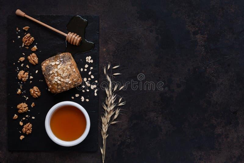 Pote de cristal con la miel, el pan y las nueces naturales frescos en un tablero de piedra Visión superior, primer, endecha del p foto de archivo