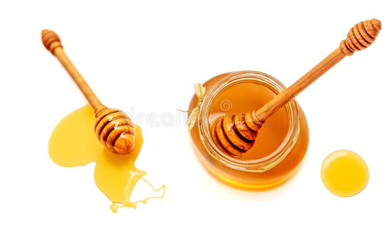 Pote de la miel y cazo de madera con el punto de colada aislado en blanco fotografía de archivo libre de regalías