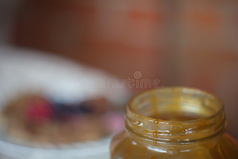 Pote de miel de colada en fondo marrón fotografía de archivo libre de regalías