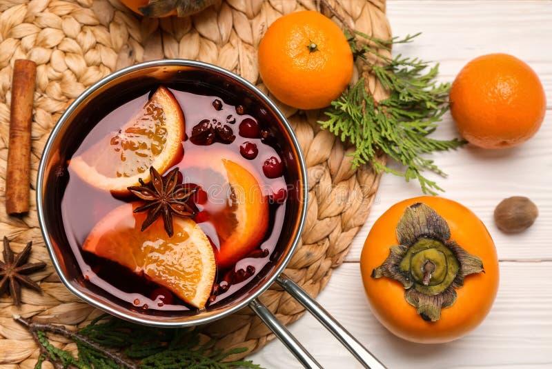 Pote de vino reflexionado sobre y de ingredientes sabrosos en la tabla imagen de archivo libre de regalías