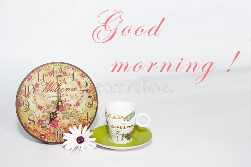 Pote del café en un platillo verde, un reloj modelado decorativo y una flor de la margarita blanca en un fondo blanco imagen de archivo libre de regalías