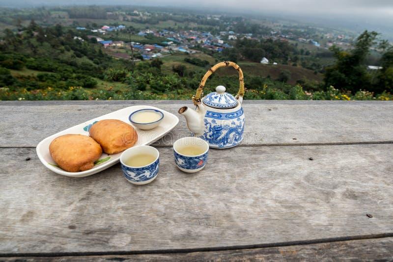 Pote del té con la taza fijada y Fried Steamed Bun en la tabla de madera delante del Mountain View imagenes de archivo