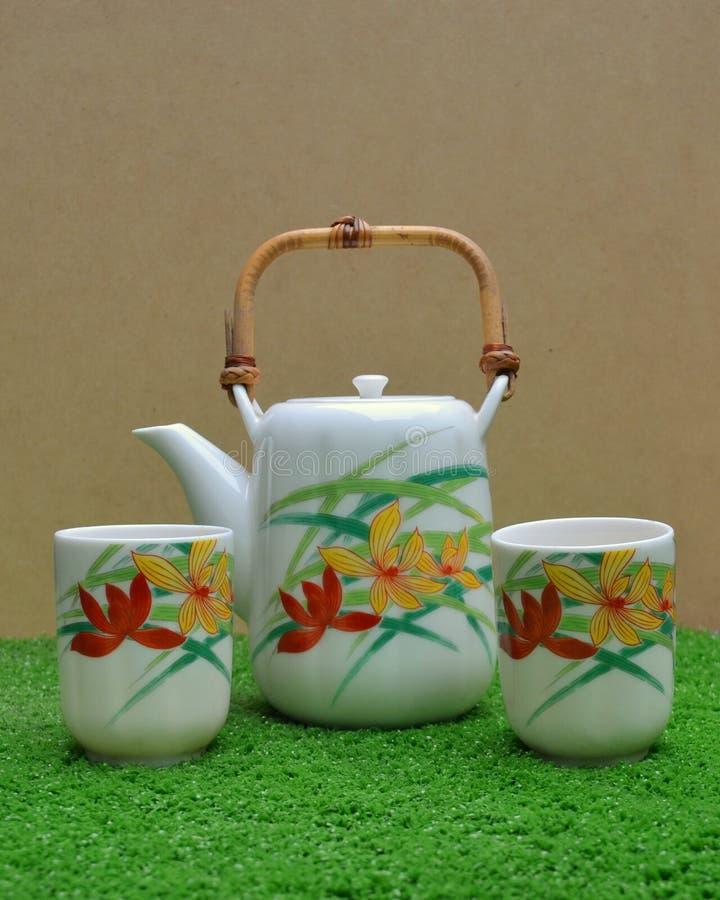 Pote del té y tazas de té con las flores pintadas a mano foto de archivo libre de regalías