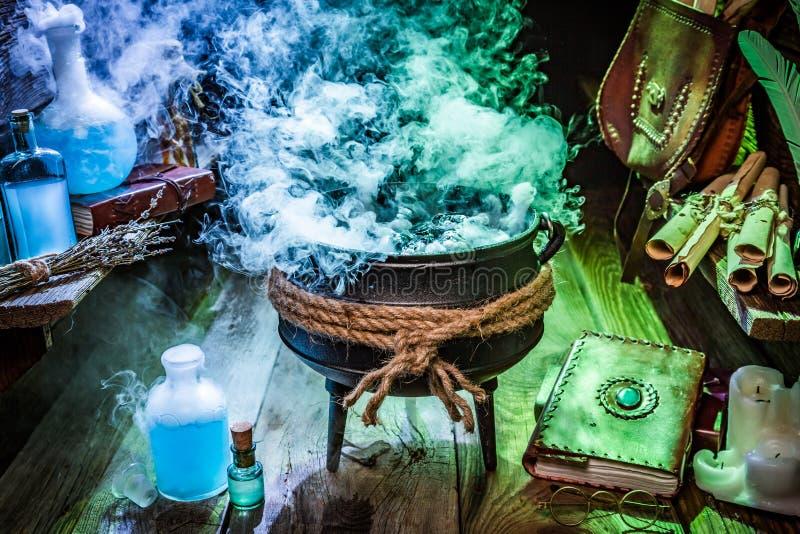 Pote misterioso de la bruja con las pociones, los libros y las volutas para Halloween imágenes de archivo libres de regalías