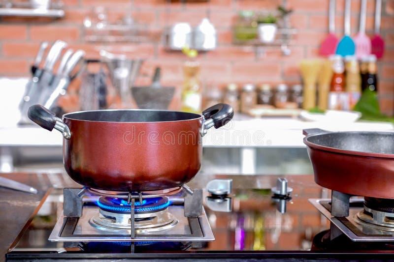 Pote y cacerola de cocinar de lujo del primer de la cocina en la estufa de gas foto de archivo libre de regalías