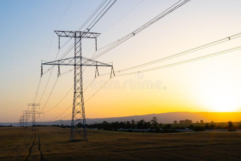 Poteau à haute tension pendant le coucher du soleil photographie stock libre de droits