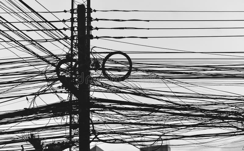 Poteau électrique avec le désordre occupé de fils trouvé au lieu du délabrement dans la ville Cette image est Siluett images libres de droits