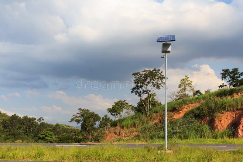 Poteau électrique avec le panneau solaire sur la route dans la campagne, utilisation d'ainsi image libre de droits