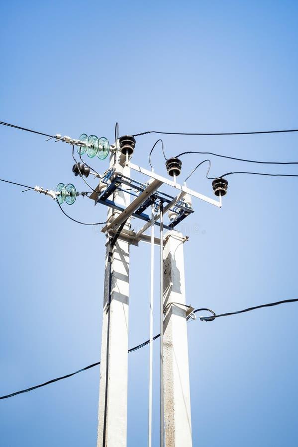 Poteau électrique avec les fils à haute tension contre le ciel bleu photographie stock libre de droits