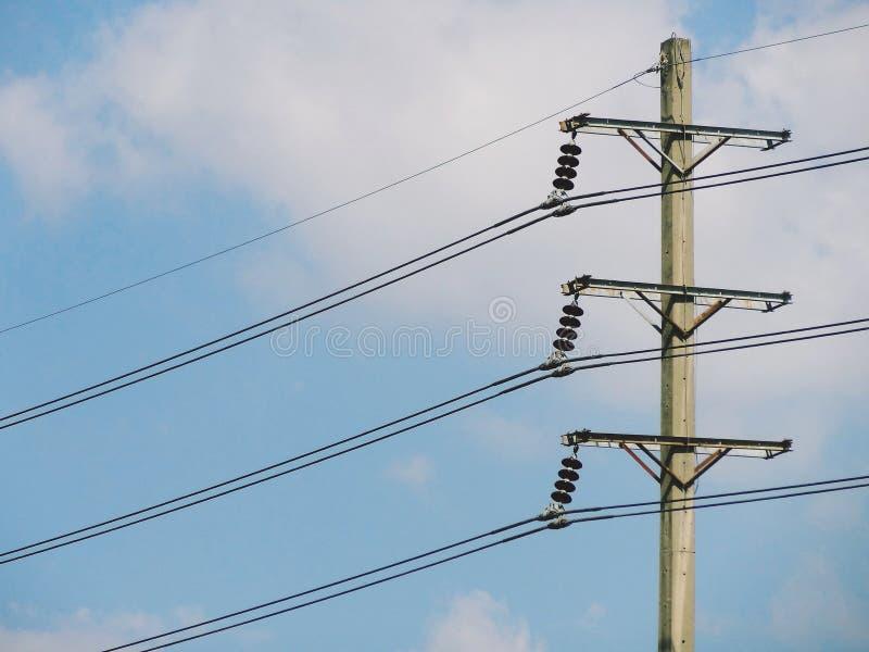 Poteau électrique de courrier de tour de ligne électrique de transmission contre le ciel bleu photographie stock libre de droits