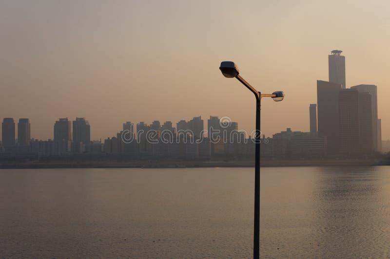 Poteau électrique faisant face à la rivière et à la ville image stock