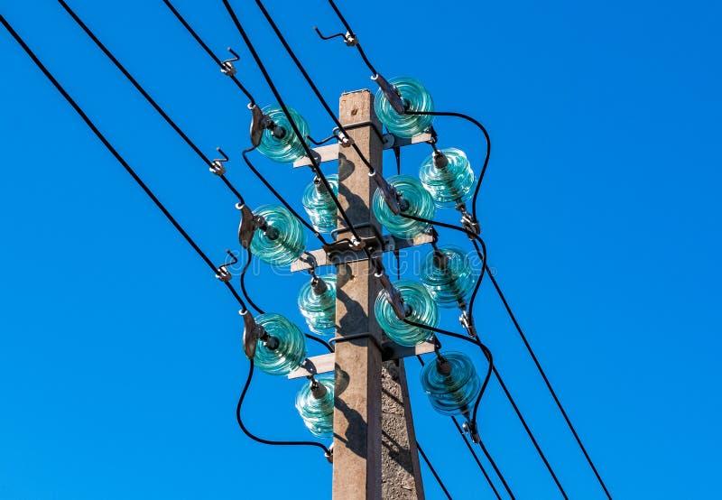 Poteau concret avec les fils électriques et les isolateurs à haute tension de distribution en tant qu'élément d'une ligne de tran images libres de droits