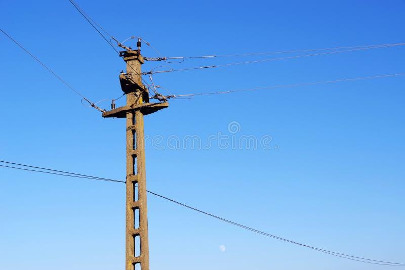 Poteau concret pour les lignes électriques aériennes contre le ciel bleu photo stock