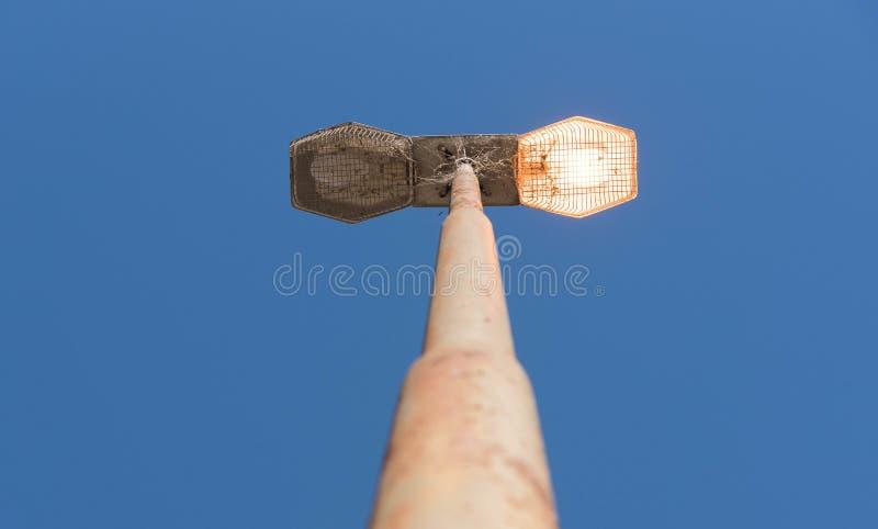 Poteau d'éclairage avec une lampe allumée images stock