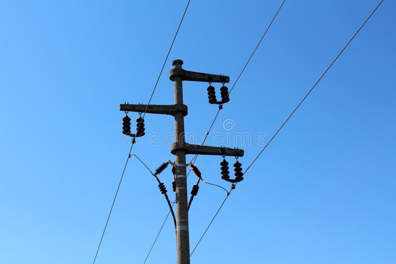 Poteau de service de ligne électrique électrique fait de béton fort avec les isolateurs en céramique multiples reliant et tenant  photo libre de droits