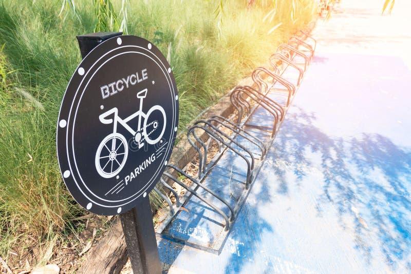 Poteau de signalisation au sujet du stationnement de bicyclette dans le park Signe de stationnement de vélo photos stock