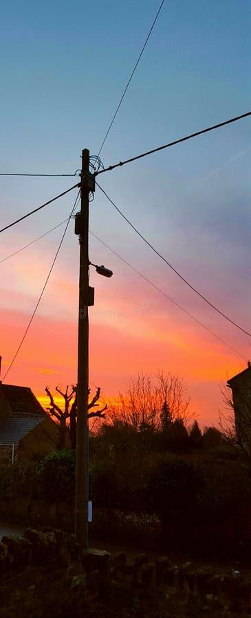 Poteau de téléphone au lever de soleil image stock