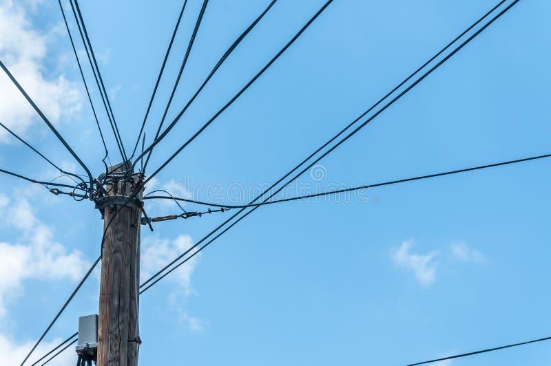 Poteau en bois de vieux rétro style avec beaucoup de fils ou de câbles électriques d'approvisionnement contre le ciel bleu photo stock