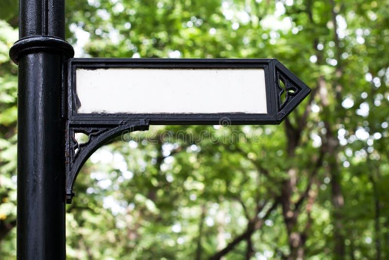 Poteau indicateur sur une colonne noire de fonte Rétro flèche d'indicateur, enseigne de conception de vintage en parc photographie stock