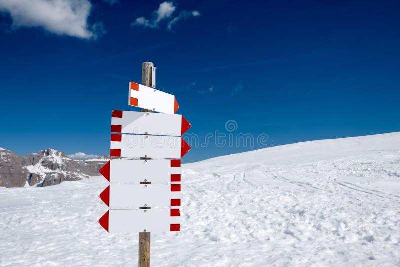Poteau indicateur vide dans les montagnes neigeuses photos stock