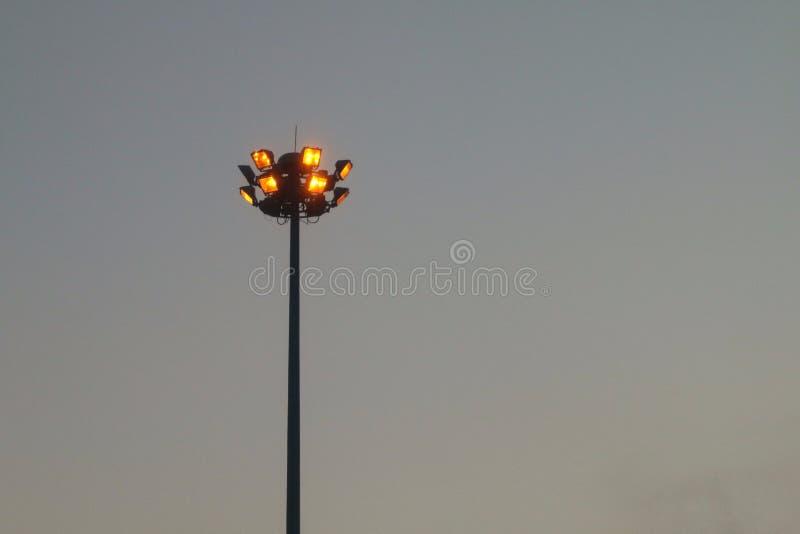 Poteau orange-clair grand sur la route, colonne d'éclairage d'autoroute la nuit images stock