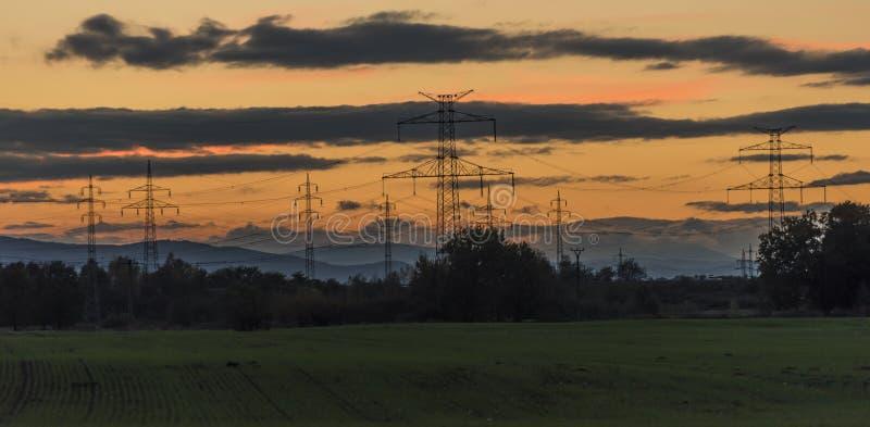 Poteaux électriques après coucher du soleil d'automne image stock