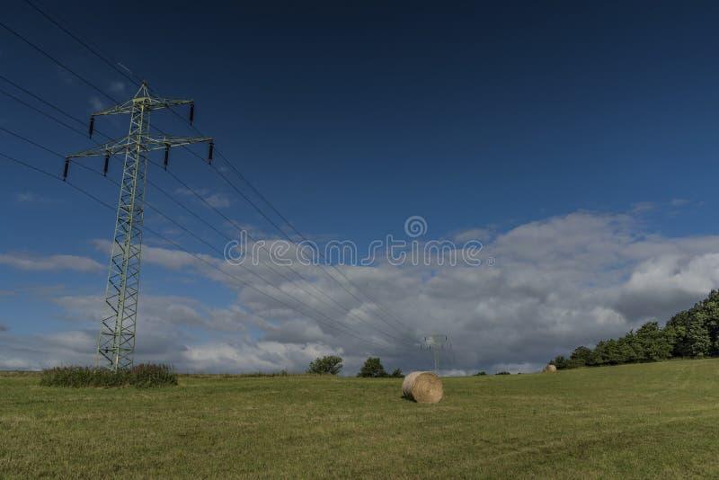 Poteaux électriques sur le pré vert avec le foin photographie stock
