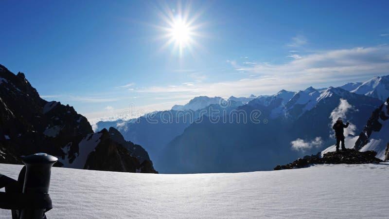 Poteaux de trekking sur le fond du soleil, des montagnes neigeuses, du ciel bleu et des nuages image libre de droits