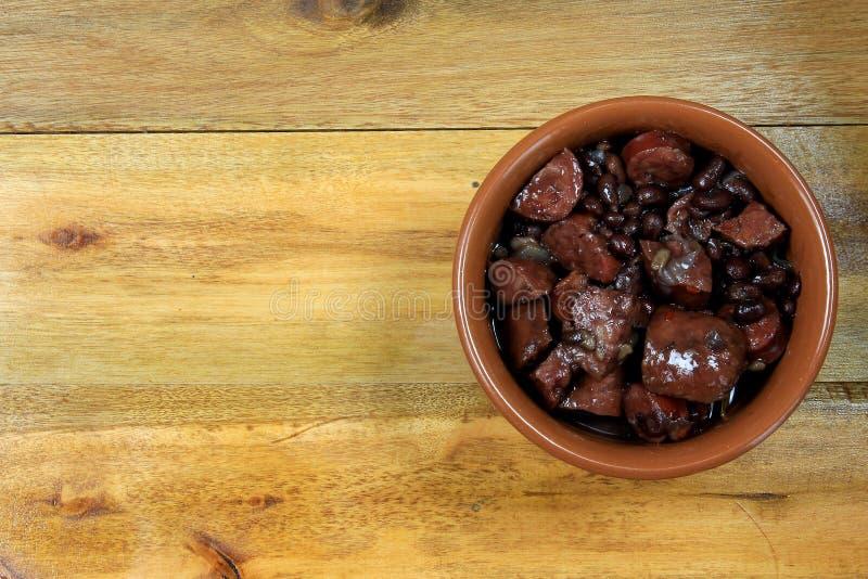 Potenciômetro com feijoada, prato brasileiro tradicional da culinária, isolado sob o fundo de madeira imagem de stock royalty free