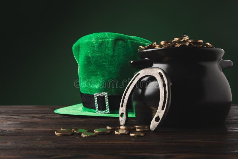 Potenciômetro com o chapéu dourado das moedas, o em ferradura e o verde na tabela fotografia de stock