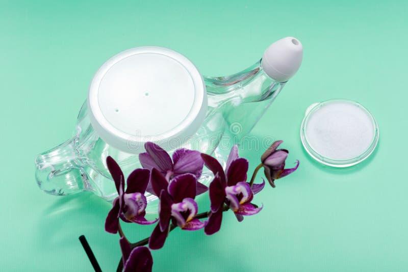 Potenciômetro com ponta macia do conforto, pilha de Neti de flores salinas e roxas da orquídea no verde Lavagem da cavidade Irrig foto de stock royalty free
