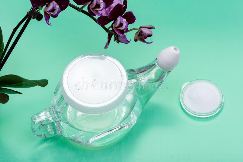 Potenciômetro com ponta macia do conforto, pilha de Neti de flores salinas e roxas da orquídea no verde Lavagem da cavidade Irrig fotos de stock royalty free