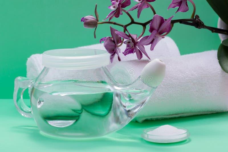 Potenciômetro com ponta macia do conforto, pilha de Neti de flores salinas, roxas da orquídea e rolado acima das toalhas brancas  imagem de stock royalty free